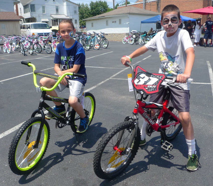 Nine-year-old Kyle Colon and his 10-year-old brother Zach Colon of Middletown pose with their new bicycles during the Wheel-A-Thon at Wesley United Methodist Church on June 30, 2018.