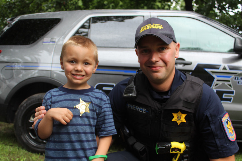 Dauphin County Sheriff's Department Deputy Josh Pierce poses with Karter Rudy during National Night Out on Aug. 7, 2018.