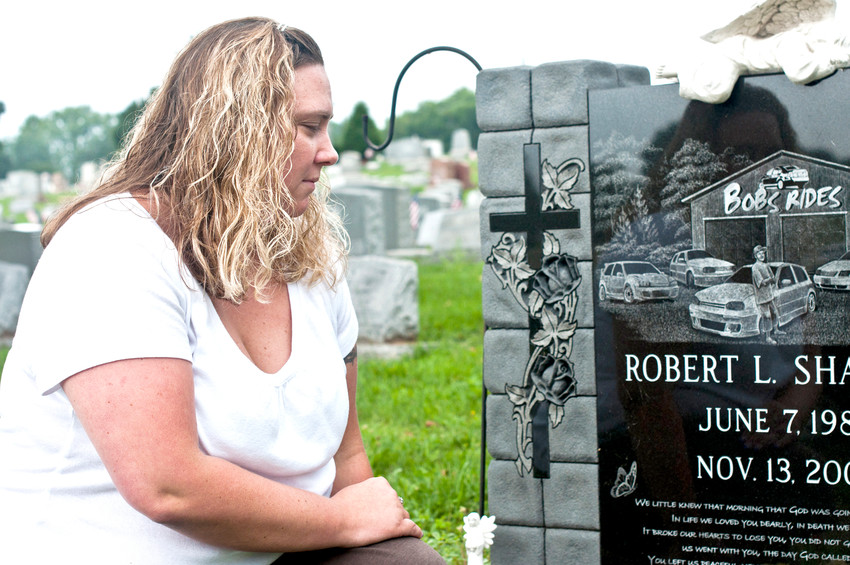 "Jessica Lawson, 31, of Middletown, visits the grave of her brother Robert L. Sharp Jr. at Middletown Cemetery several times a week. Recently, she's become concerned about people removing mementos from the headstone. ""It's hurtful,"" she said."
