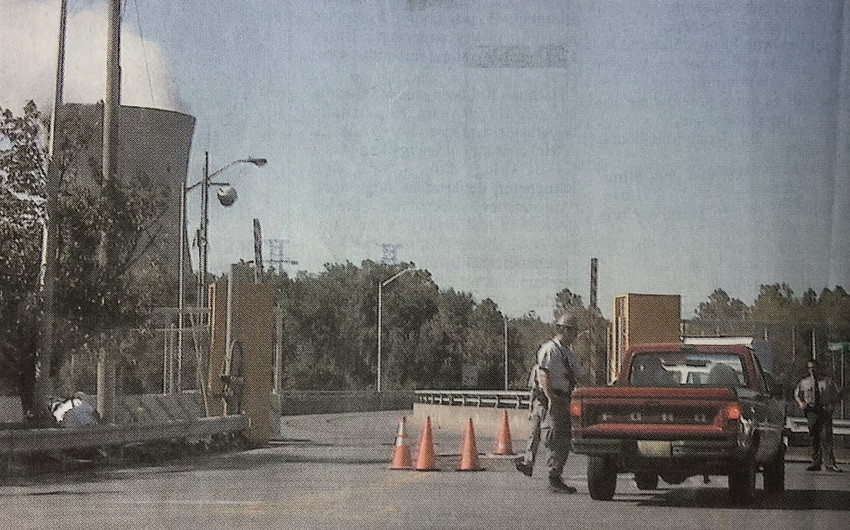 Pennsylvania State Police officers check security at the north gate of Three Mile Island while, far left, an unidentified technician in a white T-shirt works to free the heavy metal gate from its housing.