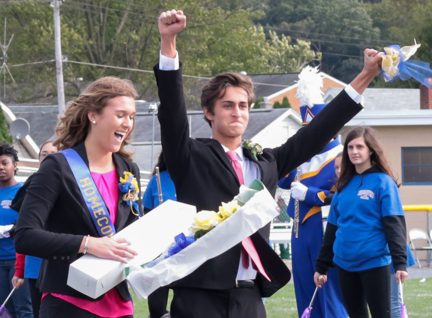 Aiden Sessa, right, celebrates as Alex Kennedy finds the yellow rose in her flower box, identifying her as the Middletown Area High School Homecoming queen during festivities Saturday at War Memorial Field.