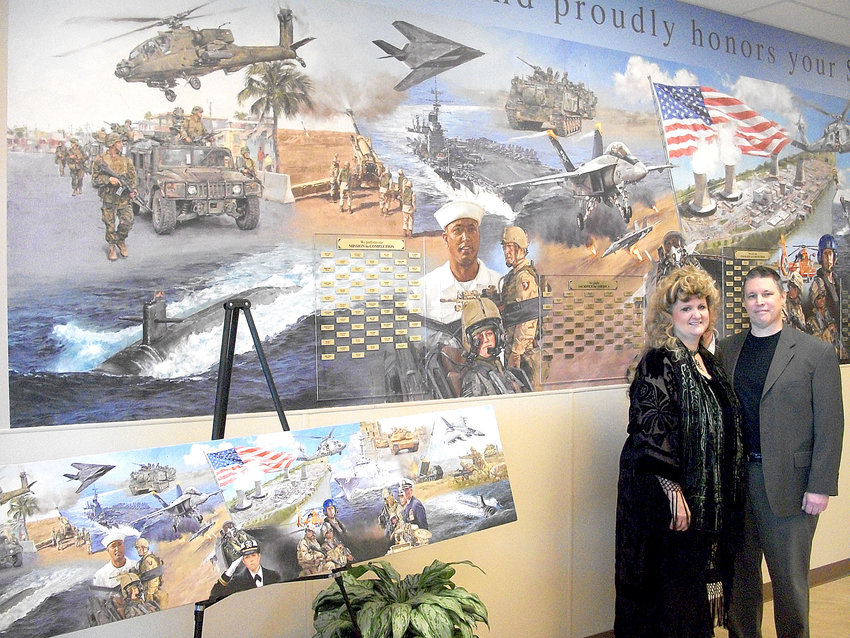 Artist Bradley Schmehl and his wife, Rebecca, a designer, pose with the mural they created inside Three Mile Island's Main Access Facility.