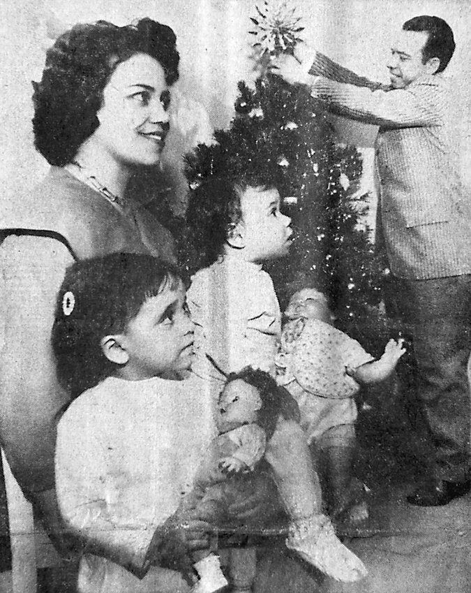 Decorating the yule tree brings smiles to Mr. and Mrs. Jose Aguero, while daughters Concepcion and Lucrecia look on with expressions that are universal for children. The Aguero family, brought to Middletown last July through sponsorship of Middletown Presbyterian Church at Union and Water streets, will spend their first Christmas in America at their Ann Street home.