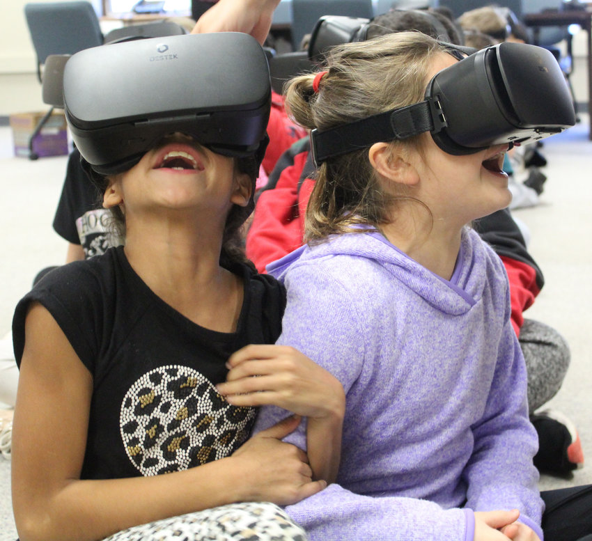 Fourth-grader Gabby Romain clings to Kaydence Zlogar's arm as they ride a roller coster on the virtual reality headset during the Girl Scouts STEM Mobile program at Kunkel Elementary School on Nov. 29.