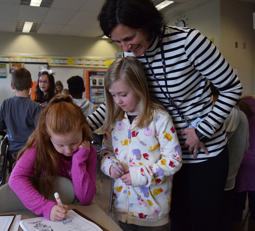 Kunkel Elementary School second-graders Audrina Mastervich and Hallie Bragunier work on a Positive Action lesson with teacher Lori D'Amour on Oct. 29.