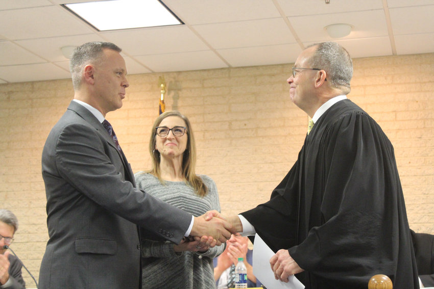New Lower Swatara Police Chief Jeffrey Vargo shakes hands with Magisterial District Judge Michael Smith after being sworn in at the Jan. 2 meeting.