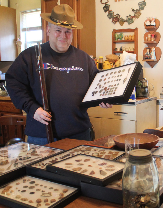 Dustin D'Agostino holds a box of coins that he has found along with some of his other finds spread across his kitchen table in his Harrisburg home.