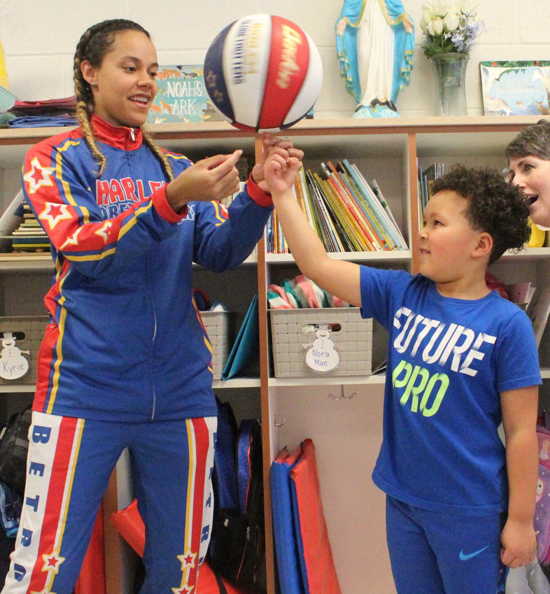 "Harlem Globetrotter Briana ""Hoops"" Green shows Kyrie Peay how to spin a ball on his finger. Green surprised Peay in his preschool classroom at Seven Sorrows on Feb. 13 with a jersey and tickets."