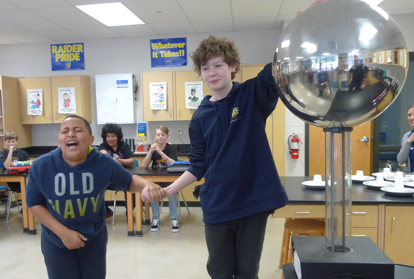 Middletown Area Middle School sixth-grader Anthony Santos, left, reacts to getting a dose of static electricity from holding the hand of fellow student Qwin Harrison, who has his other hand on a Van de Graaff generator that was provided by Phoenix Contact. Several members of Phoenix Contact spent time in the school instructing students Feb. 19-22 to celebrate National Engineers Week.
