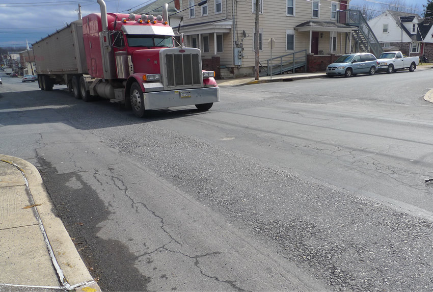 A tractor-trailer drives through the intersection of Ann and Lawrence streets over top of where a street cut had been made.