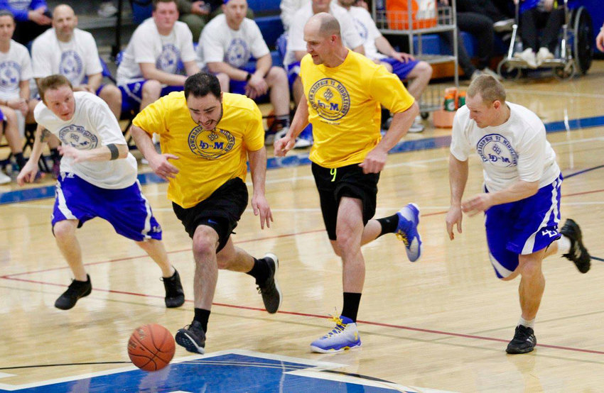 "Players from both teams chase a loose ball during the MAHS-LD ""Dunkin' for Diamonds"" faculty game Wednesday, March 6."
