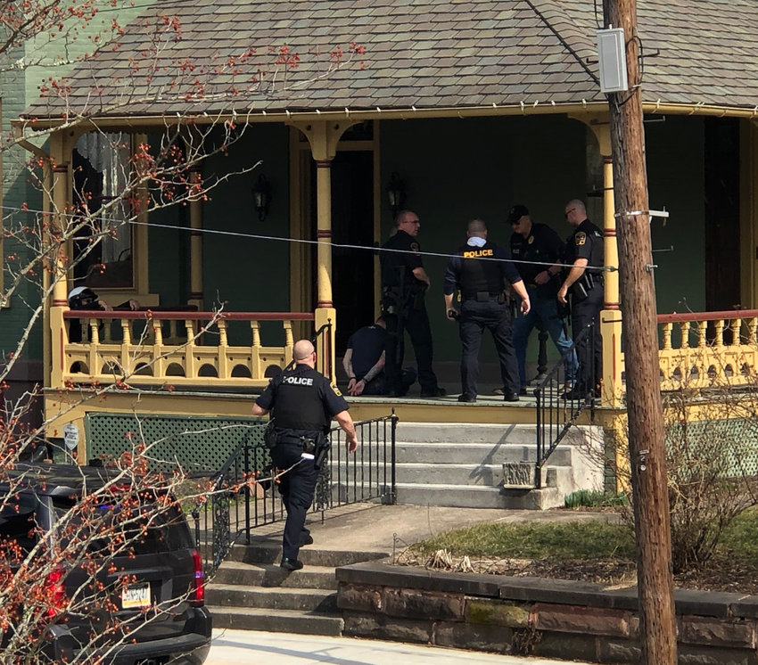 Police gather on the porch of 48 N. Union St. after taking a man who was threatening harm to himself into custody on Friday afternoon.