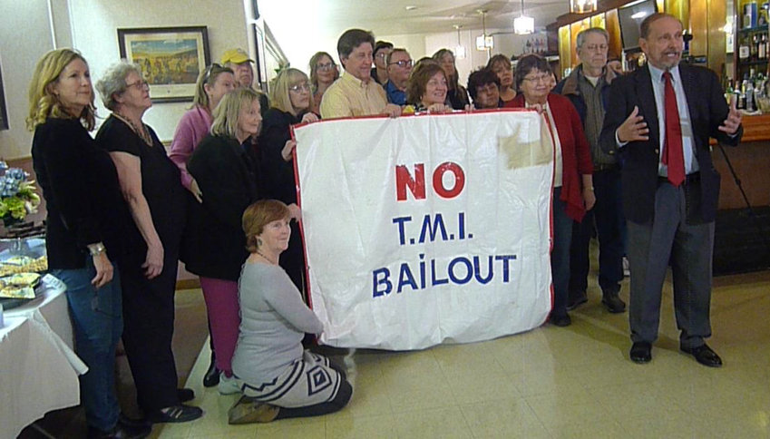 Activist Gene Stilp (right) gets ready to lead an anti-TMI bailout cheer before the start of the TMI Survivors dinner in Middletown on March 23.