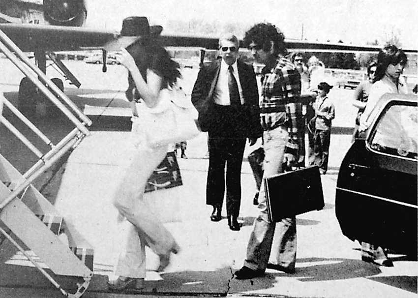 The Playboy publisher's jet made a stop at Harrisburg-Olmsted International Airport last week, carrying TV headliners Sonny and Cher to central Pennsylvania for a personal appearance in Hershey. Cher grabs her flopping hat in the breeze as she enters the sleek black jet of Hugh Hefner.