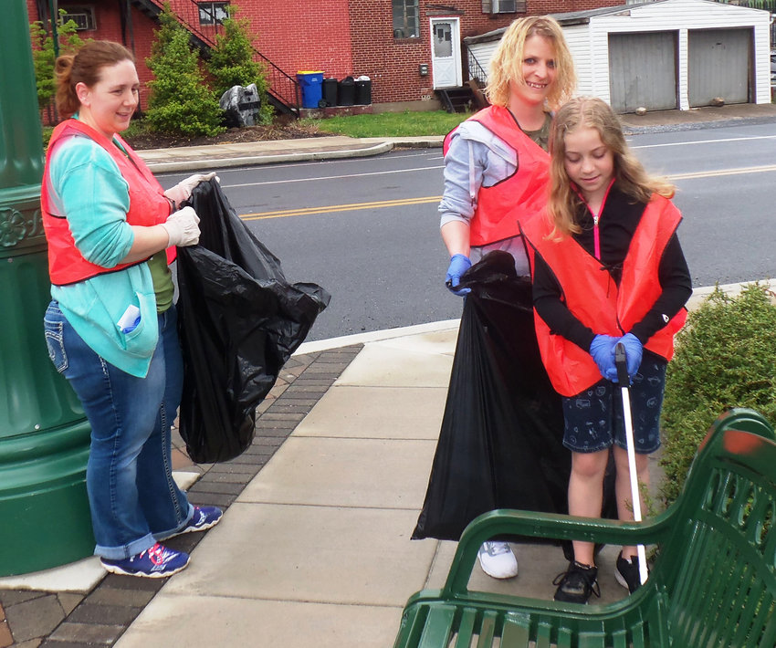 Jenna Gilman, of Harrisburg, left, cleans up a portion of South Union Street with Sarah Goughnour and daughter Moyra Goughnour, 10, of Rutherford, for Middletown Communities That Care's first Community Clean-Up Day on May 4. Gilman works with Jared Goughnour as physicial therapists at the Hetrick Center in Middletown.