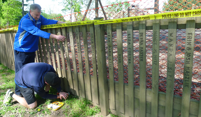Darryl Bower holds in place one of the family's wooden pickets at Kids Kastle while his son Brandon uses a drill to unscrew it in early May. The picket was one of at least six that the Bower family had purchased in 1992 to help fund construction of the playground in Hoffer Park.