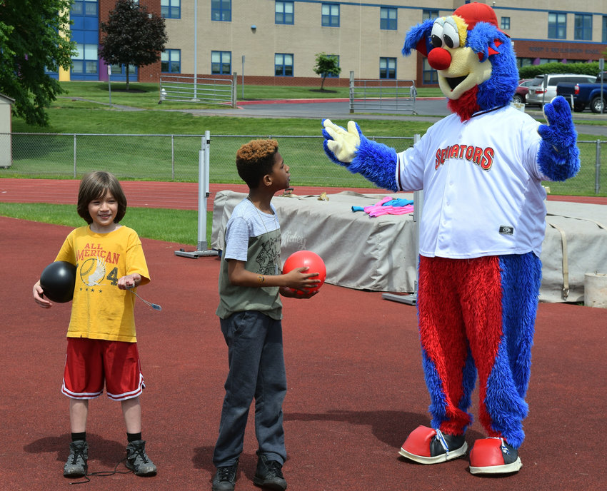Ashton White and Kayshawn Joseph talk with the Harrisburg Senators' mascot, Rascal, during the O2 Challenge on Wednesday, May 22, at the high school track.