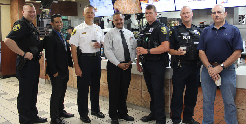 "Officer Ryan Lesko, Detective Antonio Gonzalez, Chief Jeff Vargo, McDonald's Anthony Hill, Officer Jason Heckendorn, Officer Randy Richards and Community Policing Advisory Committee member Don Bailes gathered at McDonald's on June 13 for ""Coffee with a Cop."""