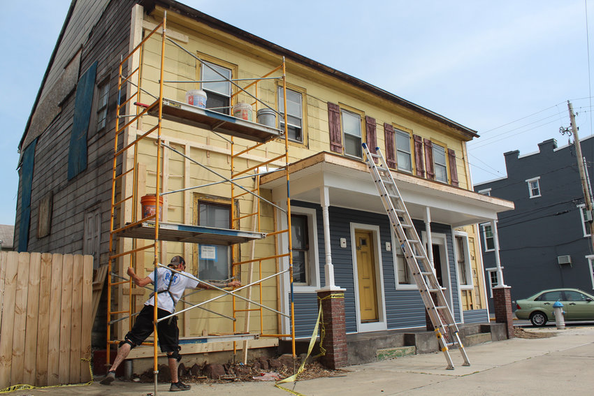 "Bob Halbleib of B&K Construction Services LLC works on the ""yellow house"" on the corner of North Union and Main streets on May 22."