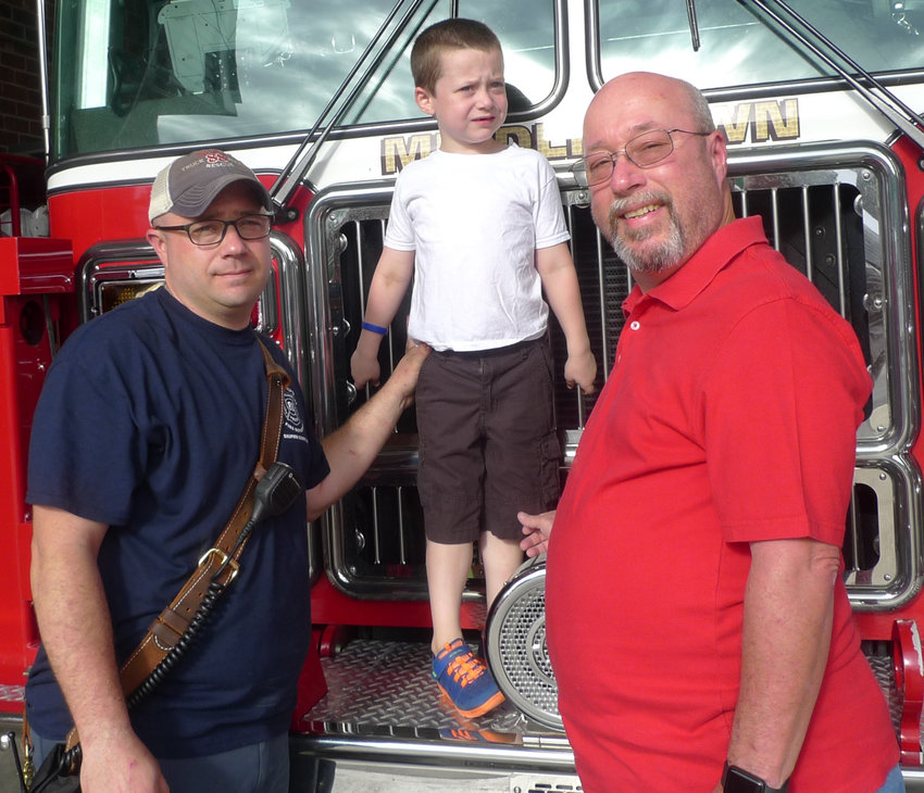 """Former Middletown Fire Chief Kenton Whitebread Sr., right, and his son, Fire Chief Kenton Whitebread Jr., flank the next generation of Whitebreads likely to serve in the fire company, 6-year-old Logan Whitebread. The back of Logan's T-shirt reads """"Future Chief."""""""