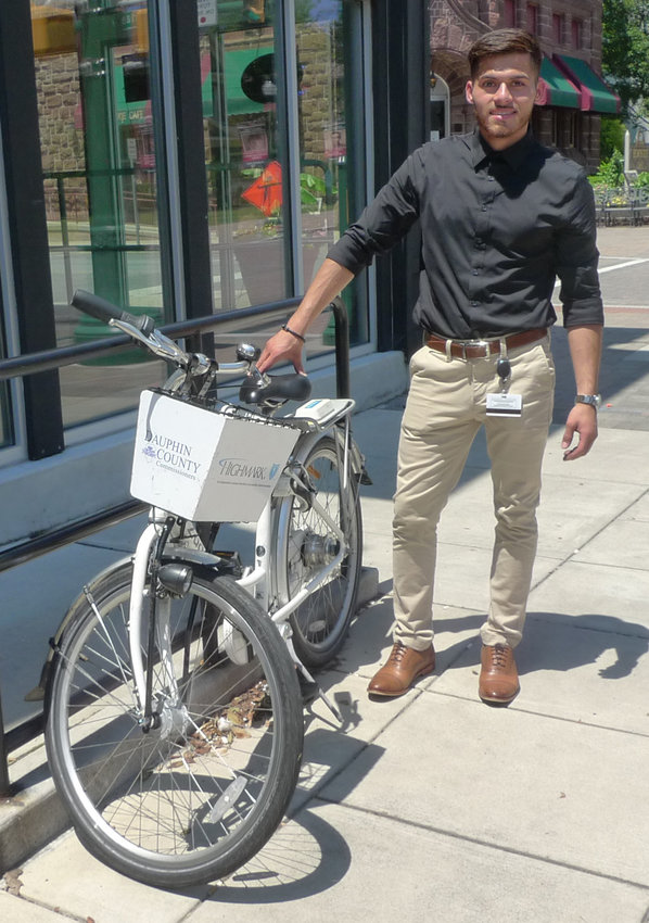 Alejandro Davila stands next to a Zagster bicycle he rented at bicycle-sharing station in Harrisburg and brought to Middletown to be locked up at a rack downtown.