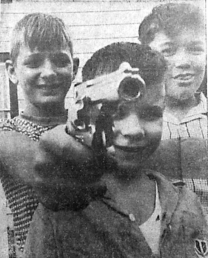 "Desperados ... three of 'em loose in Royalton, and you'd better watch out. The ""deadly"" trio with the big pistol are 10-year-old Bob Faust, son of Mr. and Mrs. Lloyd Faust, 7-year-old Paul Reismiller and his 11-year-old brother David, children of Mr. and Mrs. Charles Reismiller, all of Royalton. The children were pictured on the Fourth of July making a little noise to help celebrate the holiday."