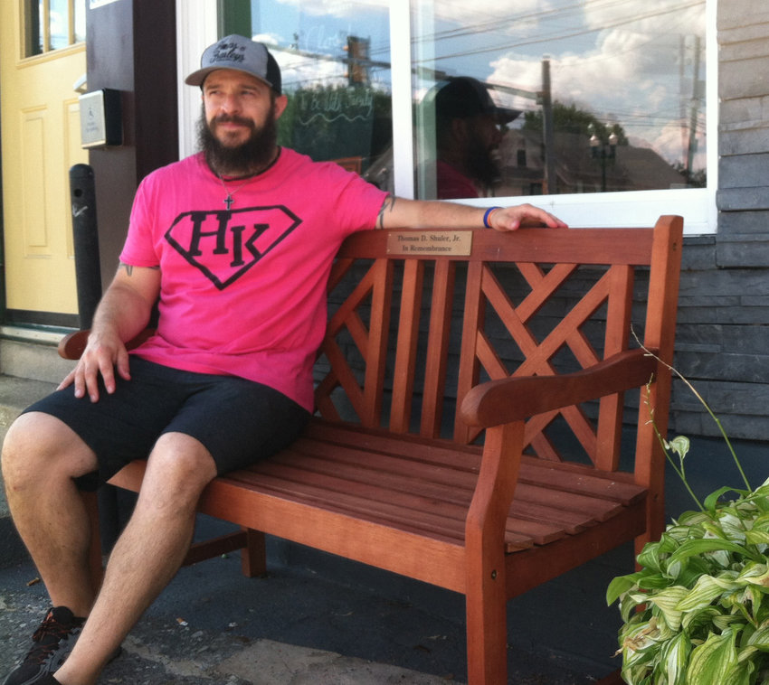 Jason Melhorn, co-owner of Hops & Barleys, sits on the bench dedicated to the memory of his father, Thomas D. Shuler Jr., who died on May 22.