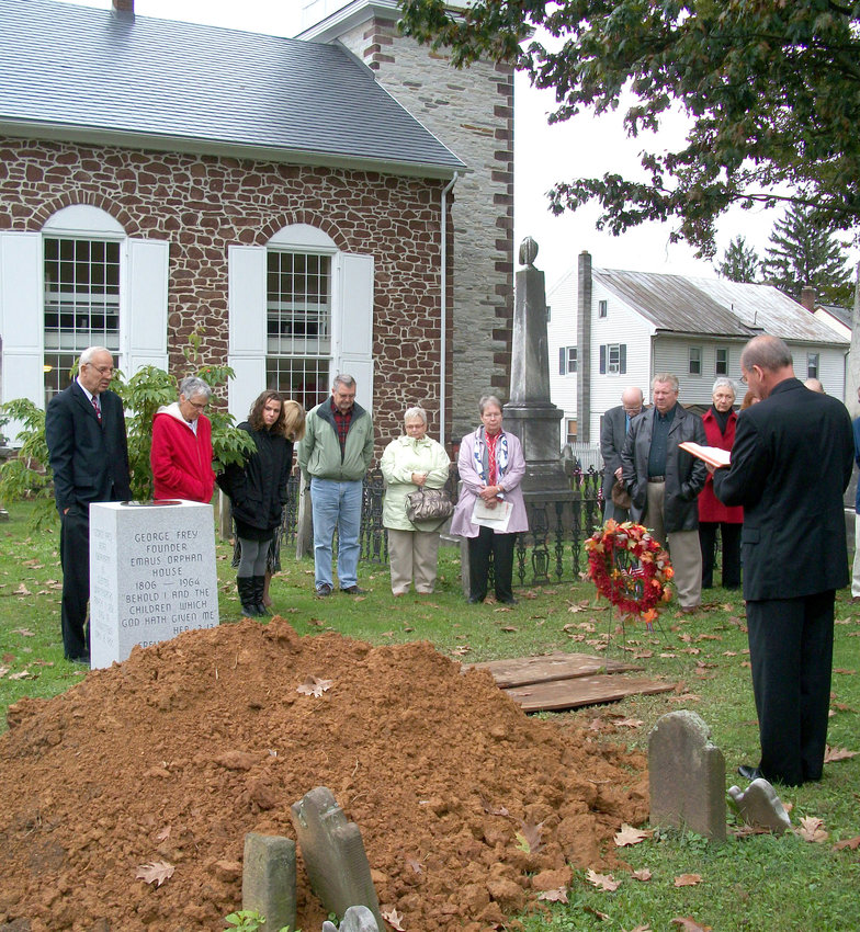 The Rev.  J. Richard Eckert of St. Peter's Lutheran Church leads mourners in prayer at the freshly dug grave of George and Anna Frey on Oct. 2, 2011.