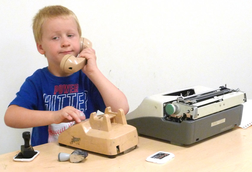 Six-year-old Carter Busey of Shippensburg makes a phone call while manning the desk at the library in Let's Pretend in Westporte Centre.