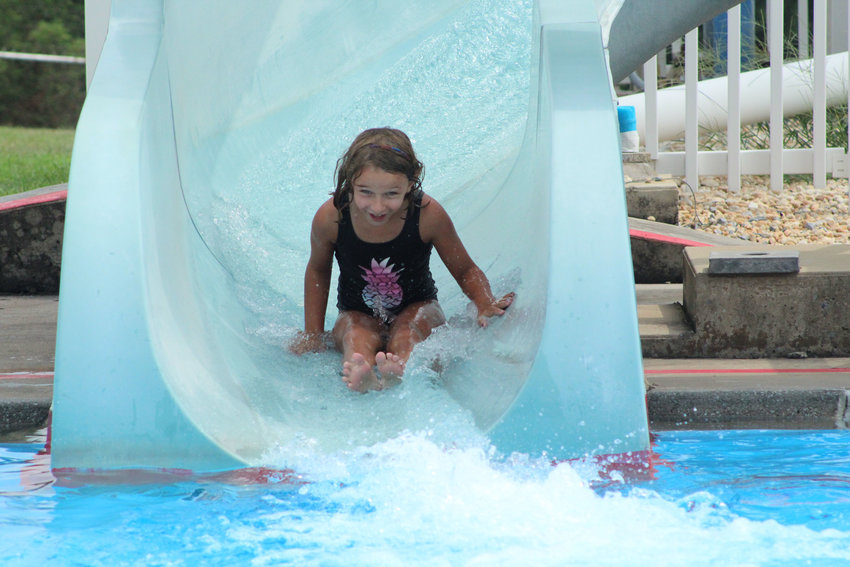 Gibson Tuffy goes down the slide at Middletown Swim Club on Aug. 16.