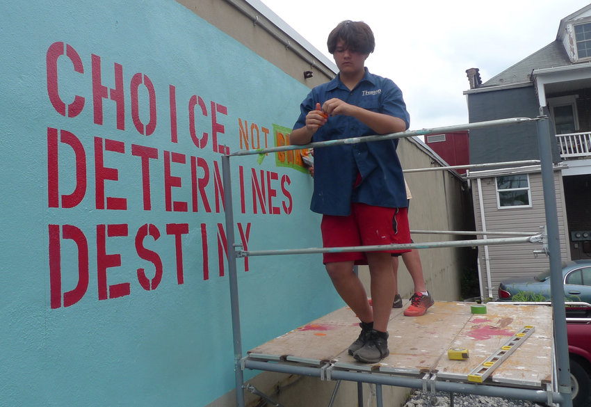Ayden Harper of Middletown Youth Corps takes a break from his work on the mural Aug. 13.