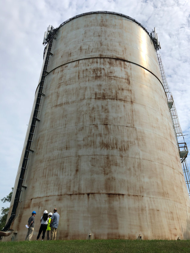 A Suez above-ground water storage tank on North Union Street towers over members of a tour.