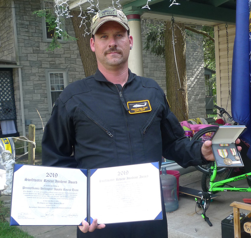 Daryl Tripp displays the Higgins & Langley Memorial Award as he stands in the front yard of his house on North Spring Street in Middletown.