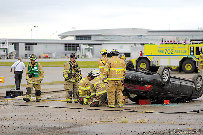 Area fire crews work to free a trapped dummy inside a car (used to simulate parts of a broken-up aircraft) at the 2016 HIA Full Scale Emergency Drill at Harrisburg International Airport on Saturday, Sept. 24, 2016.