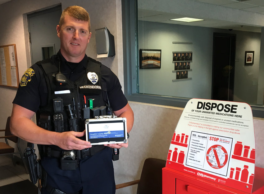 Lower Swatara Township Police Department Public Information Officer Jason Heckendorn stands with a lock box that the department is giving away to residents so that they can lock up their prescription medication.