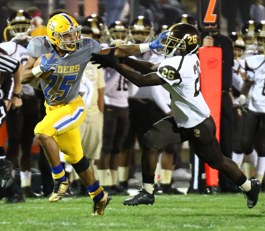 Jose Lopez stiff-arms a Milton Hershey defender on Friday during Middletown's 33-21 loss at War Memorial Field.