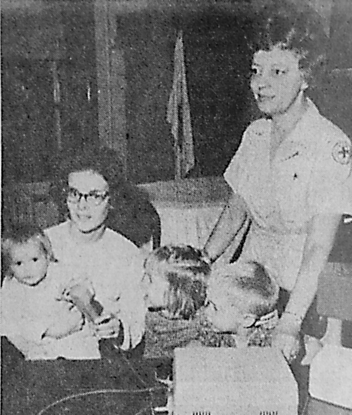 The Middletown chapter of the Red Cross is busy making free recordings of families of servicemen which are sent overseas along with a picture. Mrs. Arthur Bennage, of the local chapter, standing, watches as Mrs. Barry Miller, of Jones Street, Meade Heights, a native of Pittsburgh, holding Tammy, age 15 months, Cindy, age 4, and Barry Jr., 3, makes a recording for Sgt. Barry Miller, an Army veteran of eight years, who went to Vietnam in March. Mrs. Bennage says the program will be concluded Nov. 25, and those interested should call 944-5921 for an appointment.