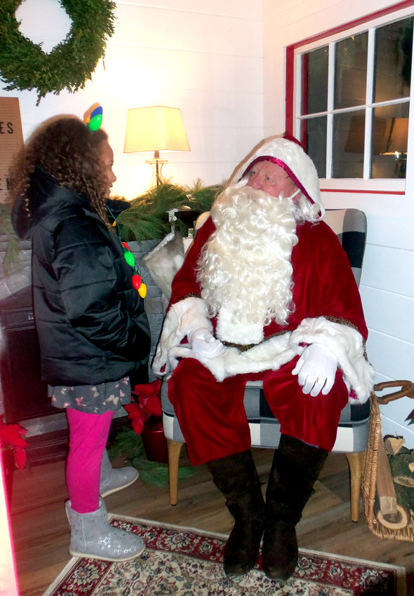 Nevaeh Buckner, 8, takes her turn with Santa Claus after the unveiling of the new Santa house at the Nov. 30 Middletown borough tree-lighting ceremony at St. Peter's Kierch.