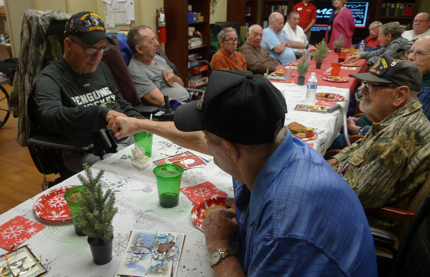 Ron Tomasetti, left, and Charles Harbold exchange fist-bumps during the holiday party held Monday for veterans at Frey Village by the American Red Cross and Royer's Flowers & Gifts.