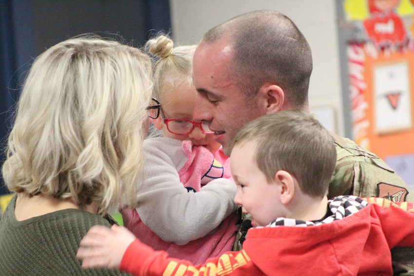 Jaclyn, Payson, Trevor and Witten Stark hug after Trevor surprised Payson at Reid Elementary School on Thursday.