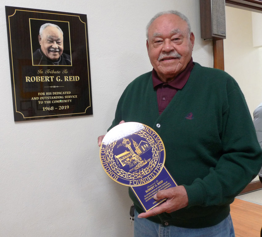 Robert Reid holds one plaque given to him by the borough, while standing next to the other plaque presented to him by borough council that will hang on the wall of council chambers on the second floor of the Municipal Building.