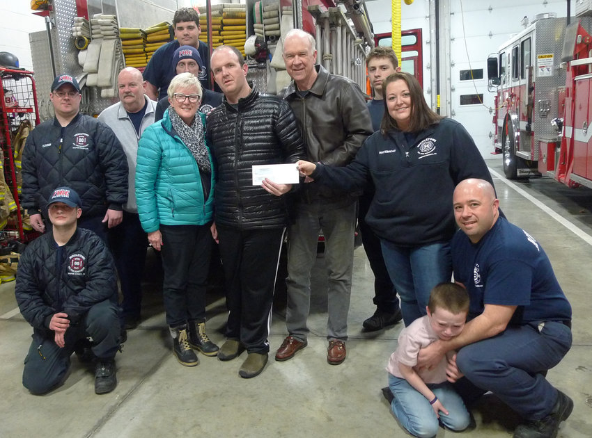 Amanda Whitebread (standing, right) presents a $1,000 donation in the name of her son Logan to Andy Ward, co-founder of Andrew's Gift, along with his wife, Dorothy. Standing between the Wards is their son Andrew, for whom Andrew's Gift is named. At right is Middletown Volunteer Fire Chief Kenton Whitebread Jr., and Logan.