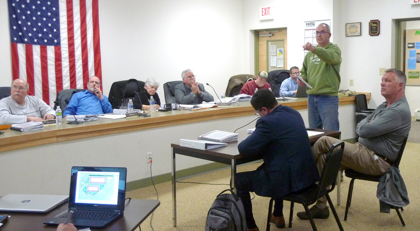 Dave Gibbs, standing, who lives near the Conewago/Londonderry township border and whose family has owned land along North Hertzler Road for generations, talks Feb. 19 about effects of the proposed warehouses during the conditional use public hearing. Seated right of Gibbs is David J. Tshudy, a lawyer representing Vision Group Ventures, and Vision Group Co-Managing Director Jeffery Camp. Seated left of Gibbs are members of the township board of supervisors and township Manager Steve Letavic.