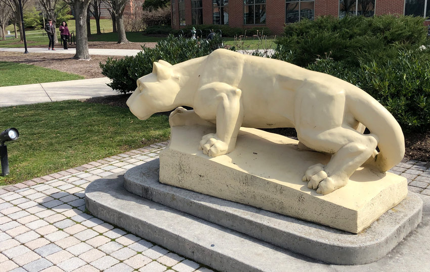 Two people walk past the Nittany lion at Penn State Harrisburg on Monday, March 16.
