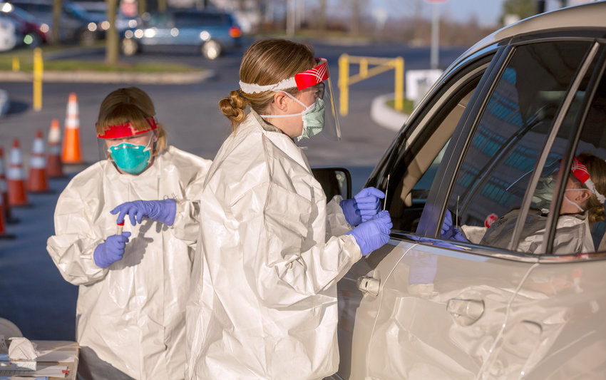 Heather Secord, a licensed practical nurse for Penn State Health, explains to a patient in their car how she will be using a swab to test for the COVID-19 virus at the drive through area on Wednesday, March 18, 2020.