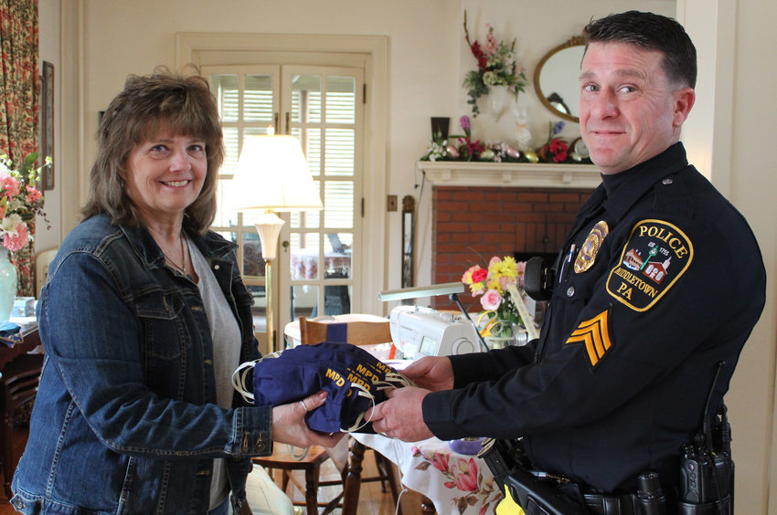 Lori Shafaye, who lives in Middletown, donates masks she made with MPD on them, courtesy of Amy Ebersole of With Kidz in Mind, to interim Middletown Police Chief Dennis Morris.