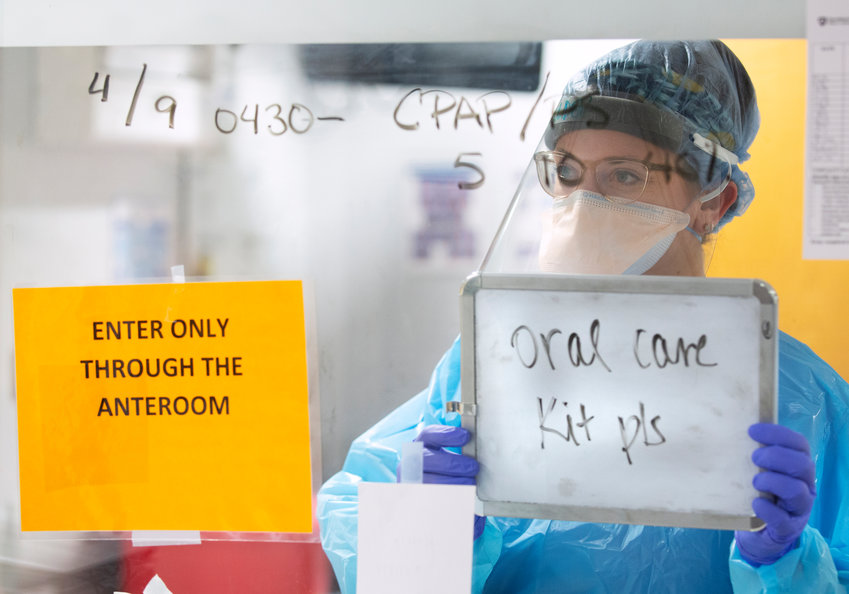 Allison Mulder, a resident nurse in the Surgical Anesthesia Intensive Care Unit at Penn State Health Milton S. Hershey Medical Center, uses a white board to communicate from the negative pressure room of a COVID-19 patient on Thursday, April 9, 2020.