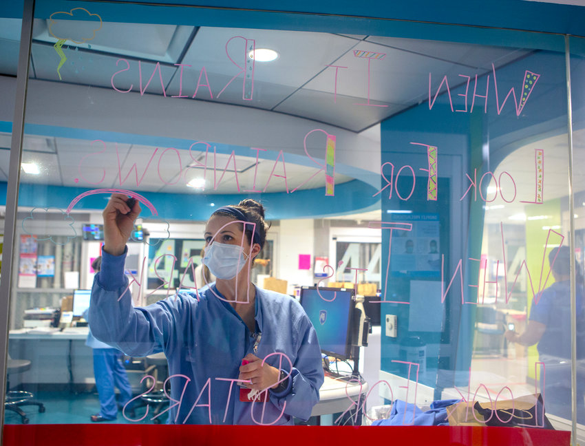 Alexa McStay, a registered nurse in the COVID-19 unit in the Pediatric Emergency Department of Penn State Health Milton S. Hershey Medical Center, writes an inspiration message on the glass in the unit on Tuesday, April 14, 2020.