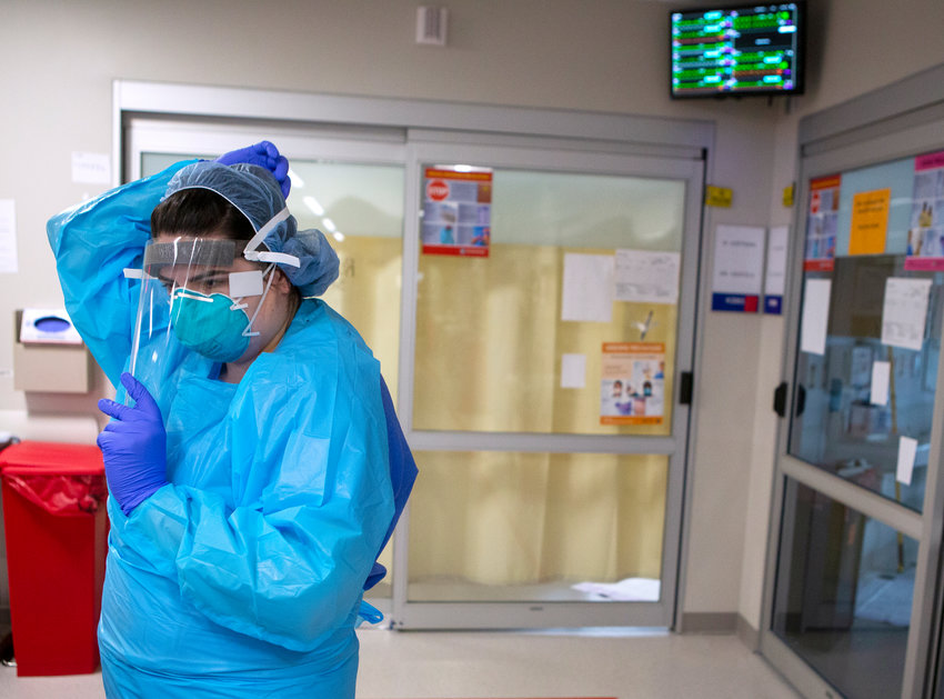 """Katlyn Ecklund, a resident nurse in the Surgical Anesthesia Intensive Care Unit, puts on personal protective equipment before entering the room of Wayne """"Huffy"""" Hoffman, a COVID-19 patient from Lebanon, on Thursday, April 9, 2020."""