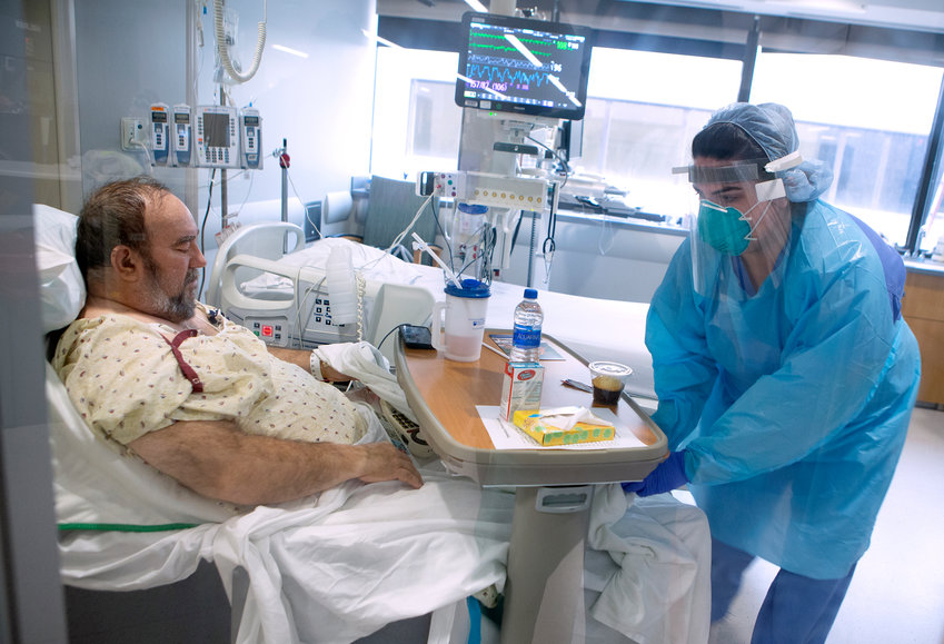"""Katlyn Ecklund, a resident nurse in the Surgical Anesthesia Intensive Care Unit at Penn State Health Milton S. Hershey Medical Center, covers the legs of Wayne """"Huffy"""" Hoffman, a COVID-19 patient from Lebanon, on Thursday, April 9, 2020."""